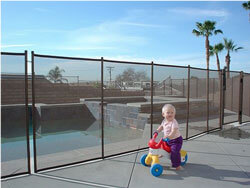 toddler on bike in front of pool fence