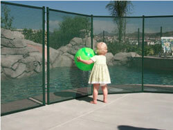 baby holding a ball beside pool fence