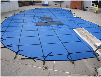 blue mesh cover on kidney-shaped pool