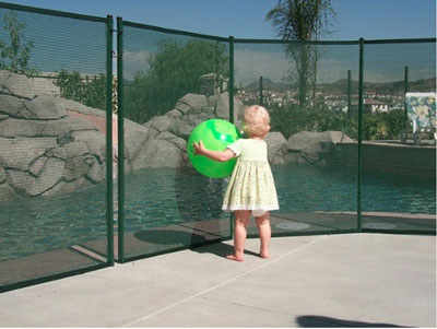 child in front of pool fence holding ball